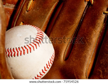 baseball in an old baseball glove - focus on the red stitching