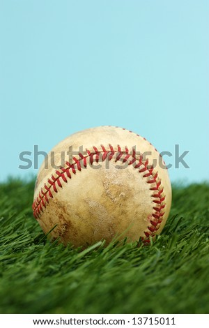 Baseball In The Green Grass With Blue Sky
