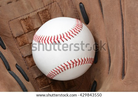 baseball in the pocket of a glove sports concept - stock photo