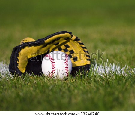 Baseball in yellow glove on the field with yard line and green grass - stock photo