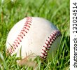 Baseball laying on green grass - stock photo