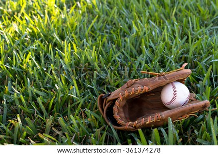 Baseball mitt and ball on grass background - stock photo