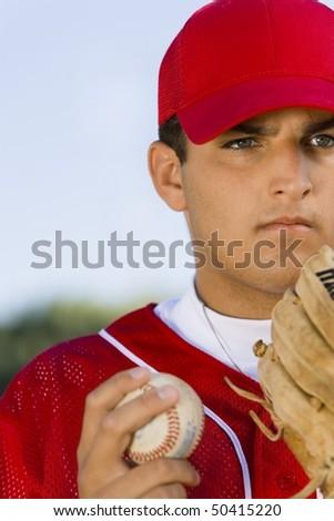Baseball pitcher holding glove and ball, (close-up) - stock photo