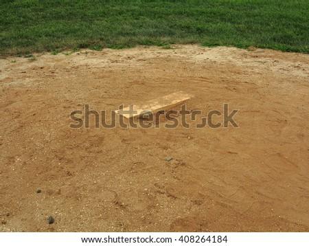 Baseball Pitching Rubber - Baseball field pitching mound with rubber. - stock photo