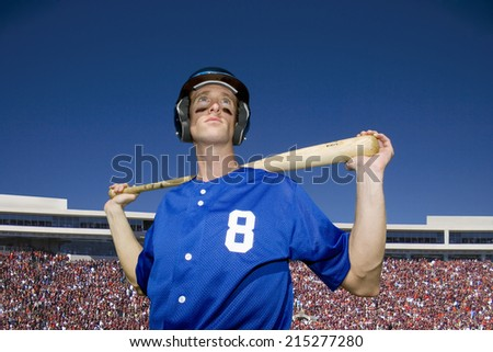 Baseball player, in number �¢â�¬��8�¢â�¬â�¢ blue uniform, helmet and face paint, standing on pitch with bat behind head, low angle view, portrait - stock photo