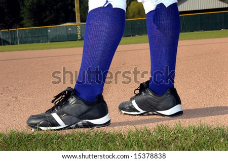 Baseball player is ready and waiting for play to begin.  His cleats are planted firmly in the infield dirt.