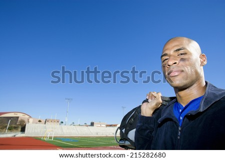 Baseball player leaving pitch post-match, carrying bag on shoulder, smiling, portrait - stock photo