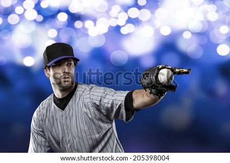 Baseball Player on a Blue Uniform on blue lights background. - stock photo