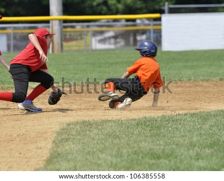 baseball player sliding into second base - stock photo