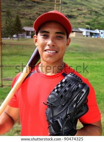 Baseball player smiles with his glove and bat - stock photo