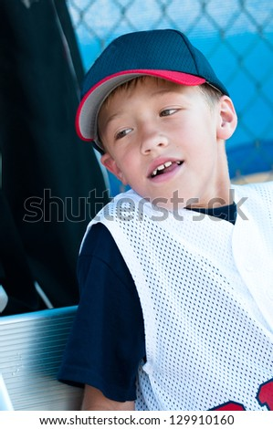 Baseball player smiling in dugout.