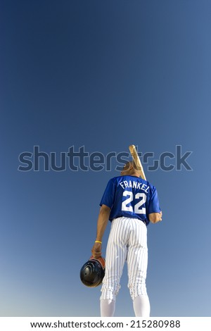 Baseball player standing against clear blue sky, carrying bat on shoulder, rear view, low angle view - stock photo