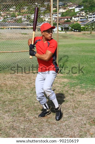 Baseball player stands at bat, ready to swing - stock photo