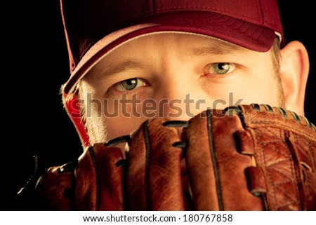 Baseball Player - This is a photo of a young man wearing a baseball cap and looking out over his glove. Shot on an black background in a warm retro color tone and processed slightly to enhance detail. - stock photo