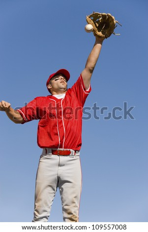 Baseball player trying to catch ball - stock photo
