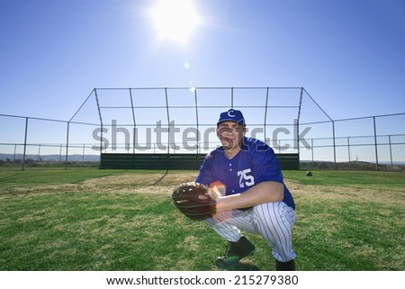 Baseball player, wearing number �¢â�¬��25�¢â�¬â�¢ blue uniform and glove, crouching on pitch, smiling, portrait (lens flare) - stock photo