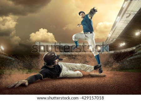Baseball players in action on the stadium. - stock photo