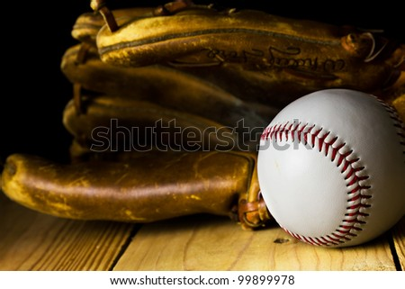 Baseball sitting in front of an old baseball glove.