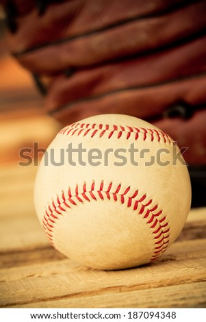 Baseball - This is a shot of an old worn baseball sitting in front of an old glove. Shot with a shallow depth of field in a warm retro color tone.