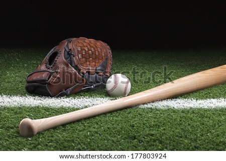 Baseball with mitt and bat on green grass with stripe at night - stock photo