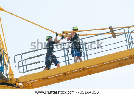 Basel, Switzerland, August 29, 2017 - Workers in the process of removing a tower crane disassembling it bit by bit. Two bolts connecting fore cable sections are being removed.