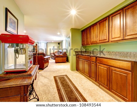 Basement interior with cabinets, green walls and popcorn machine.