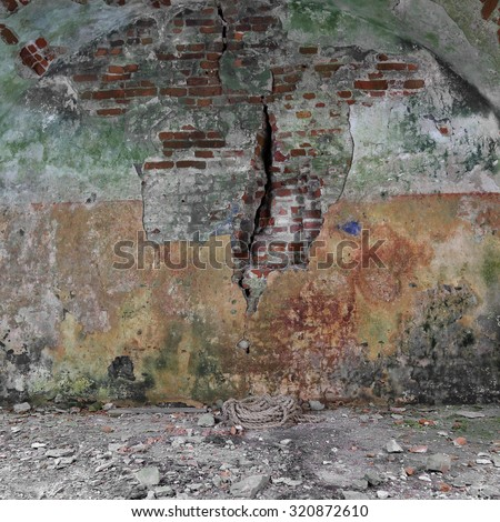 Basement of old fortress with rust and moss covered wall and rope on floor- ancient dungeons - stock photo