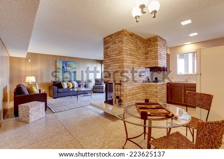 Basement open floor plan. Living room with dining and kitchen area separated with brick fireplace. Mother-in-law apartment interior