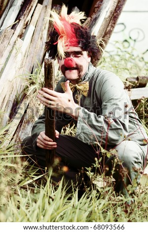 Bashful The Clown Holds A Block Of Wood While Kneeling Down Outdoors During A Malicious Portrait Of Evil Intent - stock photo