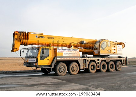 BASHKORTOSTAN, RUSSIA - DECEMBER 8, 2008: Yellow XOMG QY100K mobile crane at the interurban road. - stock photo