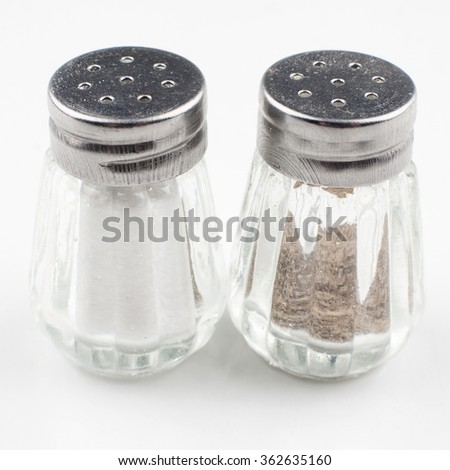 Basic condiments. Glass salt and pepper on a white background. Salt, pepper - stock photo