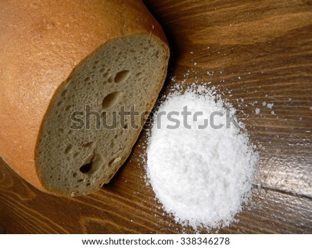 basic food loaf of bread and salt  on a wooden table - stock photo