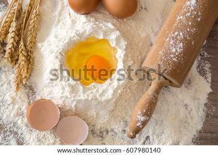 Basic ingredients for baking - eggs, dough, flour and rolling-pin on a wooden table