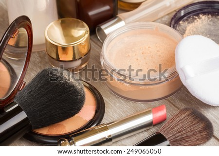Basic make-up products on table - foundation, powder and lipstick - stock photo