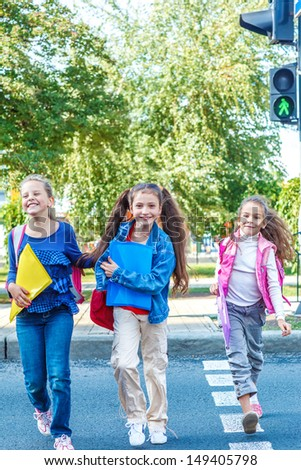 Basic school students crossing the road - stock photo