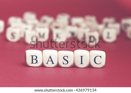 Basic word written on wood cube with red background - stock photo