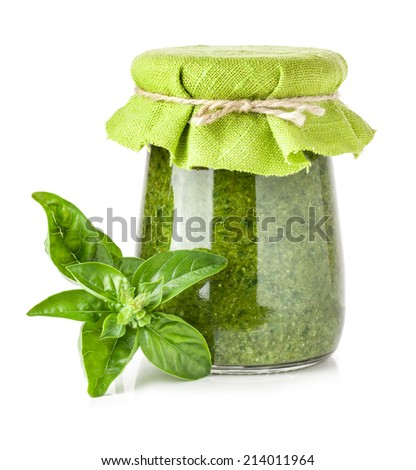 Basil and Glass jar of pesto sauce isolated on white - stock photo