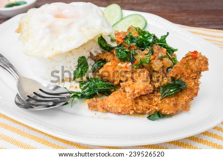 Basil fried rice with crispy chicken and fried egg (Pad kra prao kai krob), Thai food  - stock photo