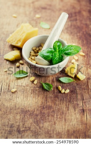 basil in a porcelain mortar and ingredients for pesto - stock photo
