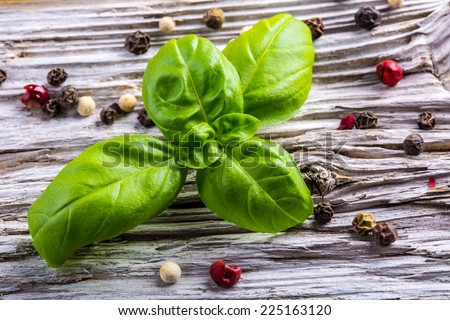 Basil leaves and pepper on a old wooden table - stock photo