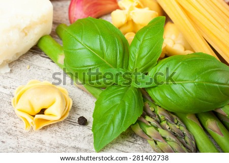 Basil leaves with homemade raw Italian tortellini, asparagus and spaghetti on withe vintage background . Selective focus. - stock photo