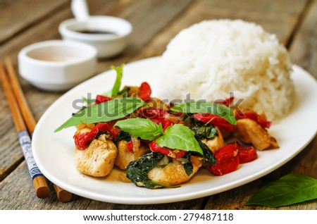 Basil pepper chicken stir fry with rice. the toning. selective focus - stock photo