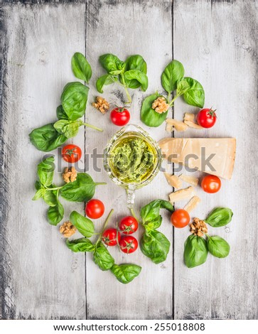 Basil pesto and ingredients: parmesan, Walnuts, and tomatoes on white old wooden table, top view - stock photo