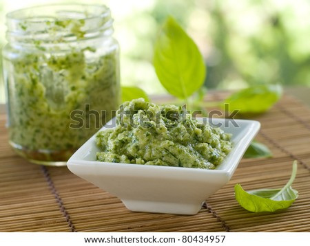 Basil pesto in a small bowl, with fresh basil leaves. Selective focus, shallow doff - stock photo
