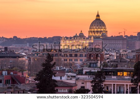 Basilica and dome of St Peter's in Vatican, Rome, lit at sunset with orange sky and rooftops