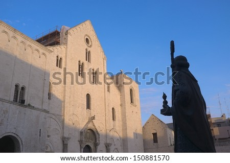 basilica and silhouette statue of St. Nicholas thaumaturge in old Town of Bari  - stock photo