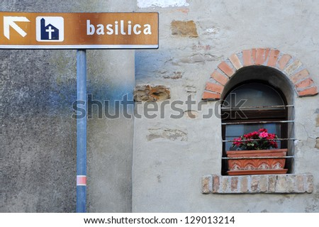 Basilica sign on the signpost and medieval window on the house wall in the town of Grado in Friuli in Northern Italy - stock photo