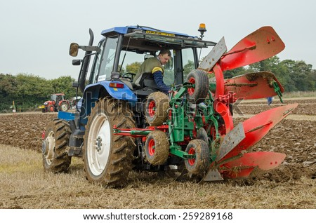BASINGSTOKE, UK  OCTOBER 12, 2014: A competitor in the one way ploughing  reversible class at the British National Ploughing Championships organised by Society of Ploughmen. Accredited photographer - stock photo
