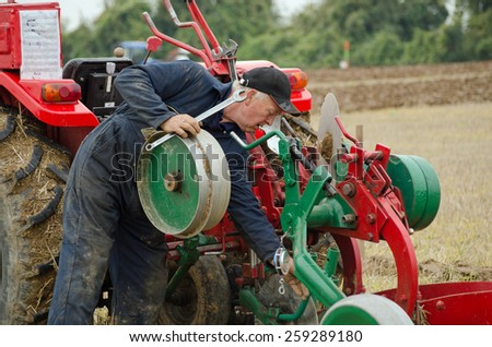 BASINGSTOKE, UK  OCTOBER 12, 2014: David Chappell adjusting his plough at the British National Ploughing Championships.  Chappell won the Semidigger, conventional plough class. Accredited photographer - stock photo