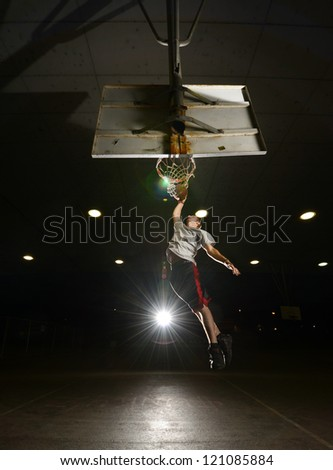 Basket and basektball player jumping with ball and aiming at basket with li - stock photo
